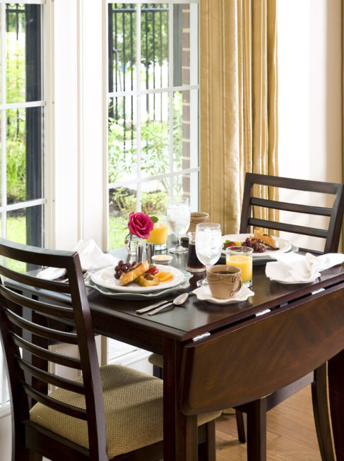 Breakfast table for two featuring pastries, orange juice, and coffee