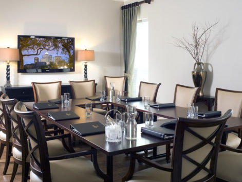 Large conference room with seating for 10, large flat screen television, and natural daylight